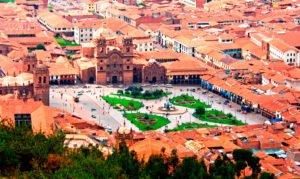 South America, Peru, Cusco, Cuzco,  Horizontal November 2006. A view of Cusco taken from a high vantage point focusing on the Main Square (Plaza de Armas). The Plaza de Armas (main square) was the centre of Inca Cusco and, still today, remains at the heart of modern Cusco. During Inca times the Plaza was known as Huacaypata (the Place of Tears or the Weeping Square) and was a place of ceremonies and military parades. It has been said that when the Inca's conquered new lands they would bring back some of the soil to be mixed with the soil of Huacaypata, as a symbolic gesture to incorporate the newly gained territories into the Inca empire.  The Plaza was once flanked with Inca palaces. The remains of the ancient walls of Inca Pachacutec's palace can still be seen on the north-west side of the square, inside the Roma Restaurant close to the corner of the Plaza and Calle Plateros. The northern and western sides of the Plaza are now lined by arcades with shops and travel agencies. There are many restaurants, bars and coffee shops with beautifully carved wooden balconies overlooking the Plaza - a great place to relax and enjoy the view. The Plaza's north-eastern edge is dominated by the Cathedral which is flanked on the right-hand side by the El Triunfo church. On the south-east side is the smaller but more ornate church of La Compania de Jesus with its impressive pair of belfries.